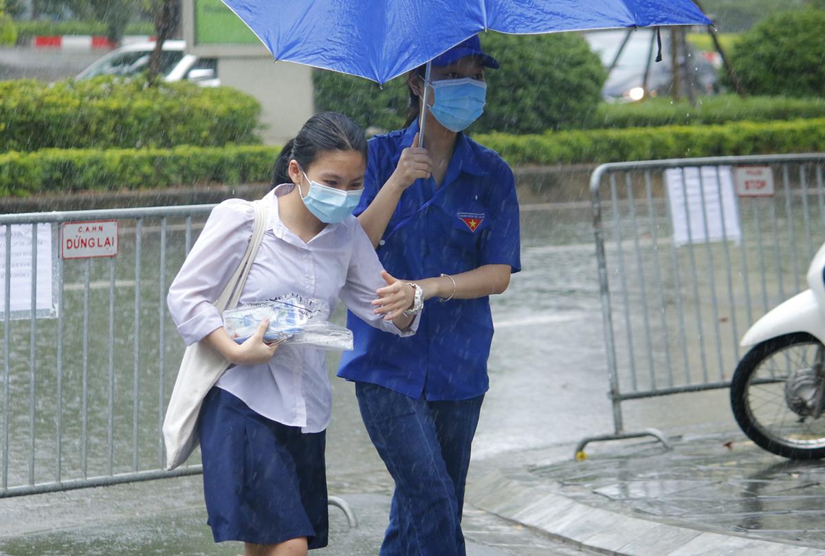 Thí sinh ở điểm thi trường THCS Yên Hoà, Cầu Giấy được tình nguyện viên hỗ trợ di chuyển tới phòng thi. Ảnh: Thanh Hằng.