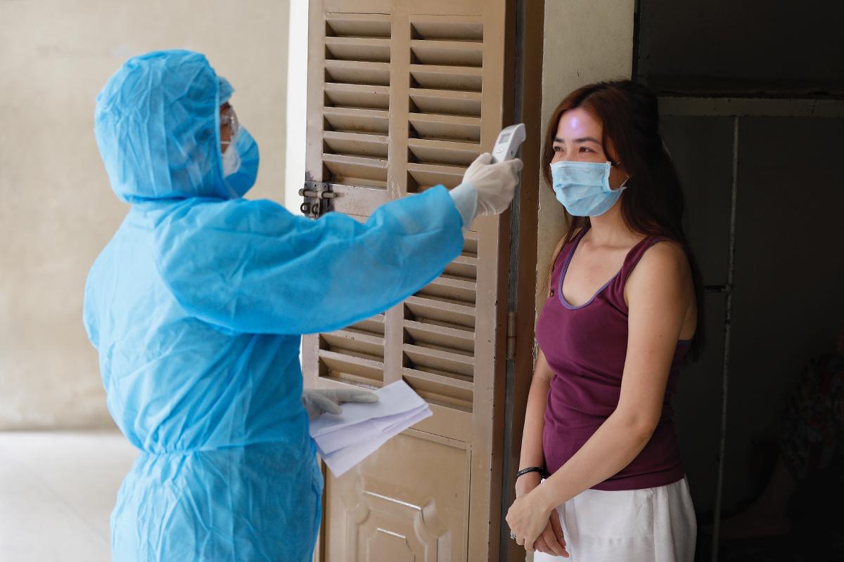 Nhân viên y tế đang kiểm tra sức khoẻ người cách ly tập trung tại Trung tâm Giáo dục Quốc phòng - An ninh (Đại học Quốc gia TP HCM), tháng 5/2021. Ảnh: Hữu Khoa.