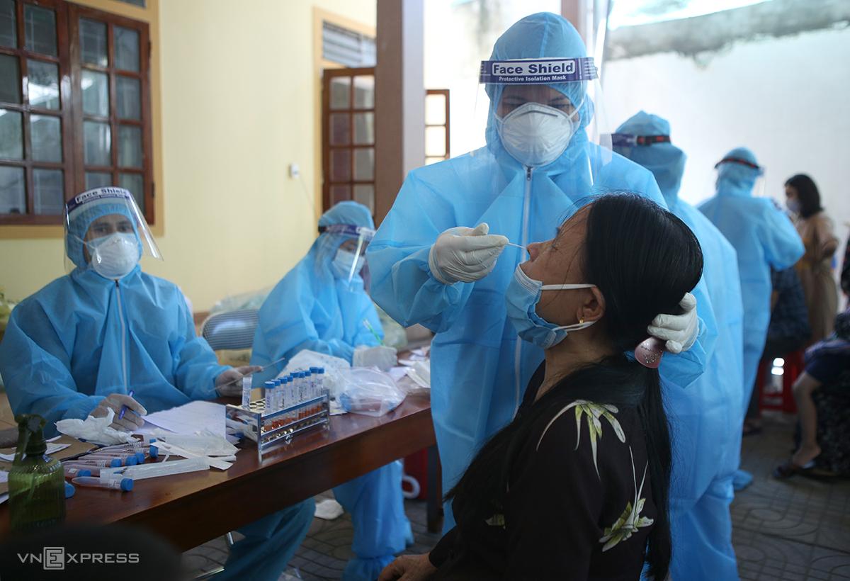 Cán bộ y tế lấy mẫu xét nghiệm cho người dân phường Hà Huy Tập nằm trong khu vực bị phong tỏa, sáng 14/6. Ảnh: Nguyễn Hải