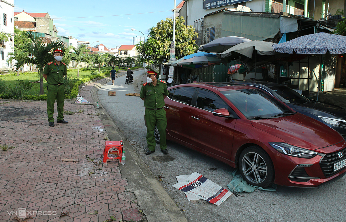Công an chốt chặn ngõ dẫn vào khu dân cư bị phong tỏa, lúc 7h ngày 14/6.  Ảnh: Nguyễn Hải