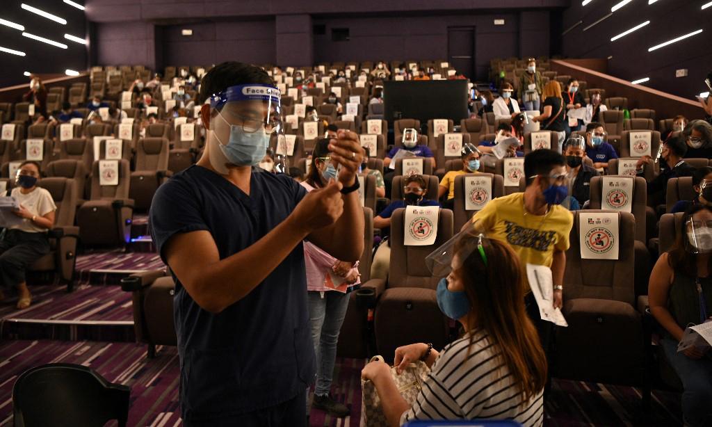 Nhân viên y tế chuẩn bị tiêm vaccine Covid-19 cho người dân bên trong một rạp chiếu phim được dùng làm điểm tiêm chủng ở ngoại ô Manila, Philippines, hôm 14/6. Ảnh: AFP.