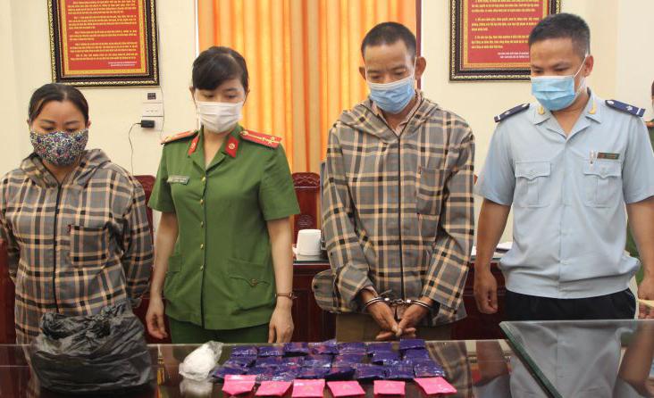 Hai nghi phạm Hà Thị Mạch và Lục Văn Sáo (áo kẻ sọc) bị bắt cùng lô hàng cấm. Ảnh: Lam Sơn.