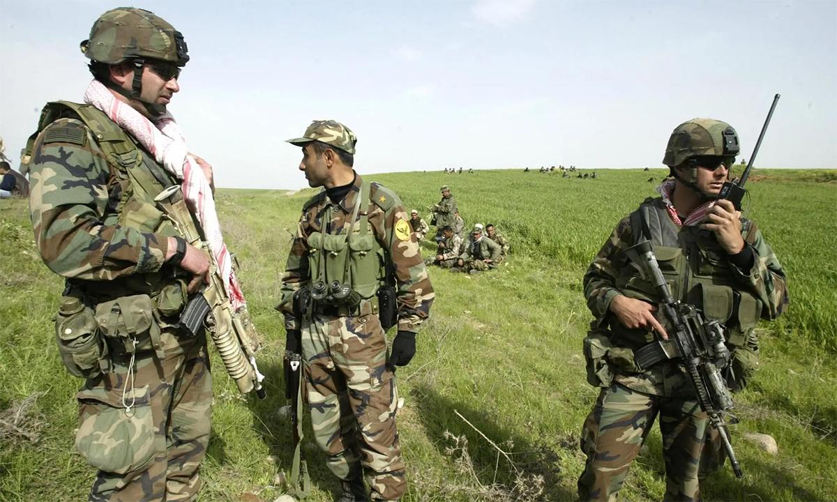 Binh sĩ Mỹ (trái và phải) cùng dân quân Peshmerga của người Kurd (giữa và phía sau) bên ngoài làng al-Nazimiya tại Iraq tháng 4/2003. Ảnh: AFP.