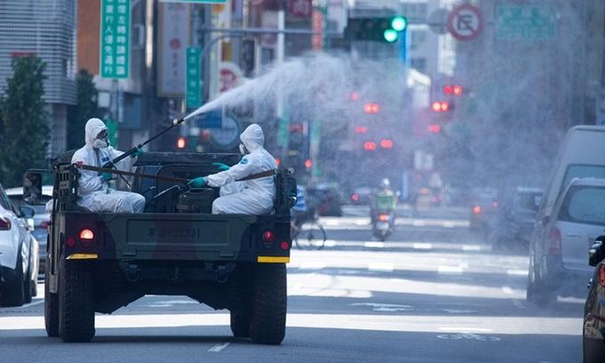 Nhân viên y tế phun khử trùng một con phố ở thành phố Đài Bắc, Đài Loan, hôm 16/5. Ảnh: VCG.