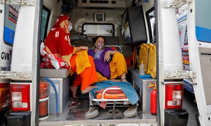 Một bệnh nhân Covid-19 thở oxy trong xe cứu thương để chờ nhập viện ở thành phố Ahmedabad, hôm 20/4. Ảnh: Reuters.