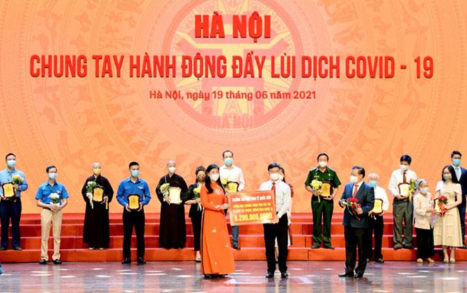 Đại diện trường Đại học Kinh tế quốc dân trao tượng trưng 8,2 tỷ đồng tại chương trình Chung tay hành động đẩy lùi dịch Covid-19 tối 19/6 ở Hà Nội. Ảnh: NEU.