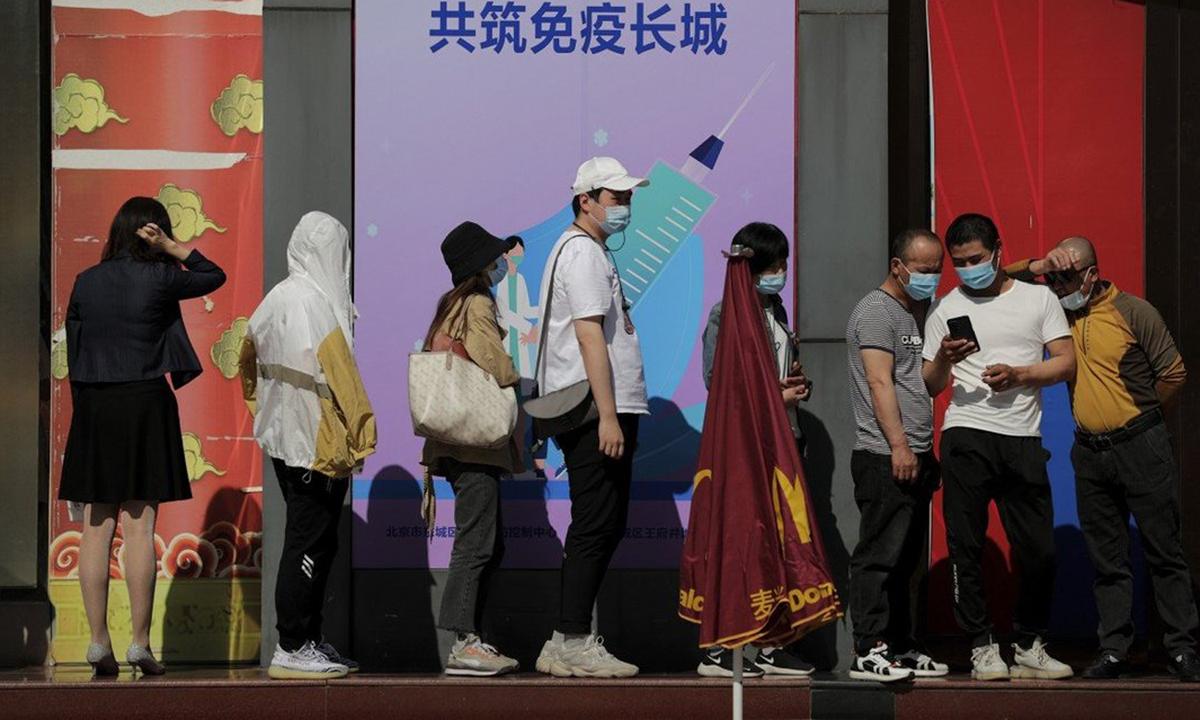 Người dân xếp hàng trước một điểm tiêm chủng ở Bắc Kinh. Ảnh: AP.