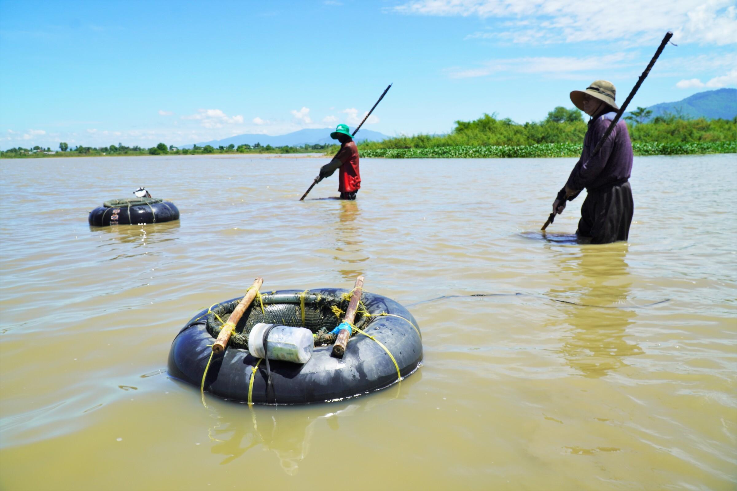 Ông Mạnh (phải) cùng đồng nghiệp cào hến ở hồ thủy lợi huyện Hàm Thuận Bắc, ngày 17/6. Ảnh: Việt Quốc.