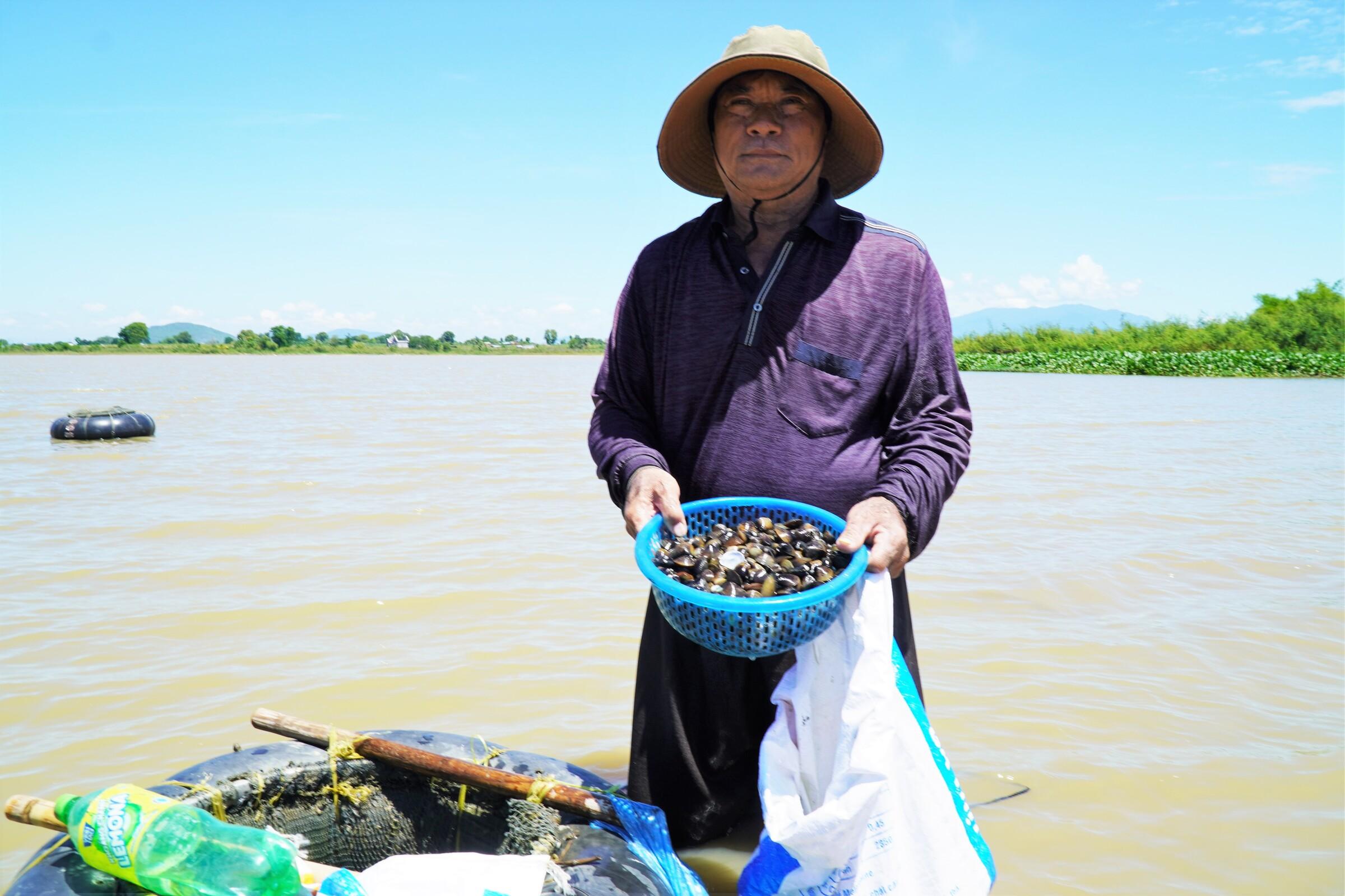Ông Nguyễn Văn Mạnh đang múc hến đổ vào bao sau 5 giờ ngâm mình cào hến. Ảnh: Việt Quốc.