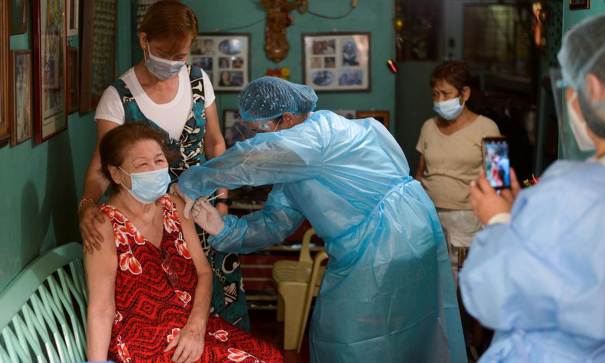 Nhân viên y tế tiêm chủng vaccine Covid-19 tại nhà dân ở Manila, Philippines hôm 21/5. Ảnh: Reuters.