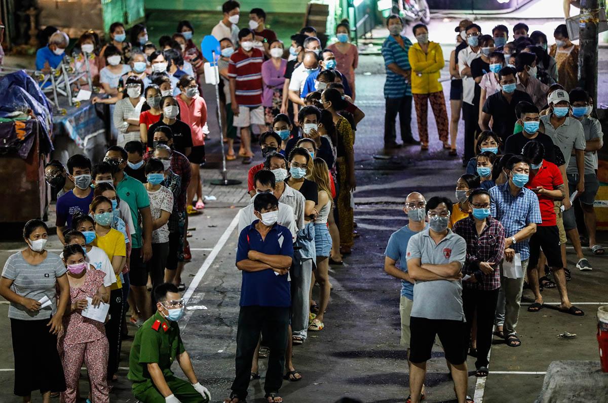 Người dân quận Bình Tân xếp hàng lấy lẫu xét nghiệm, tối 22/6. Ảnh: Hữu Khoa.