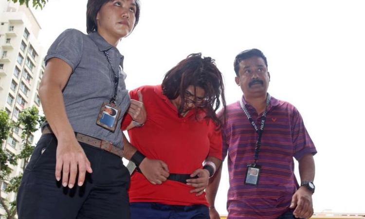 Gaiyathiri Murugayan (áo đỏ) bị cảnh sát Singapore áp giải về nhà riêng để điều tra hồi tháng 8/2016. Ảnh: AFP.