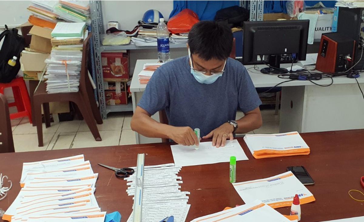 Giáo viên trường THPT Nguyễn Du (quận 10) kiểm tra giấy báo dự thi trước khi gửi thư cho thí sinh, sáng 23/6. Ảnh: Nhà trường cung cấp.