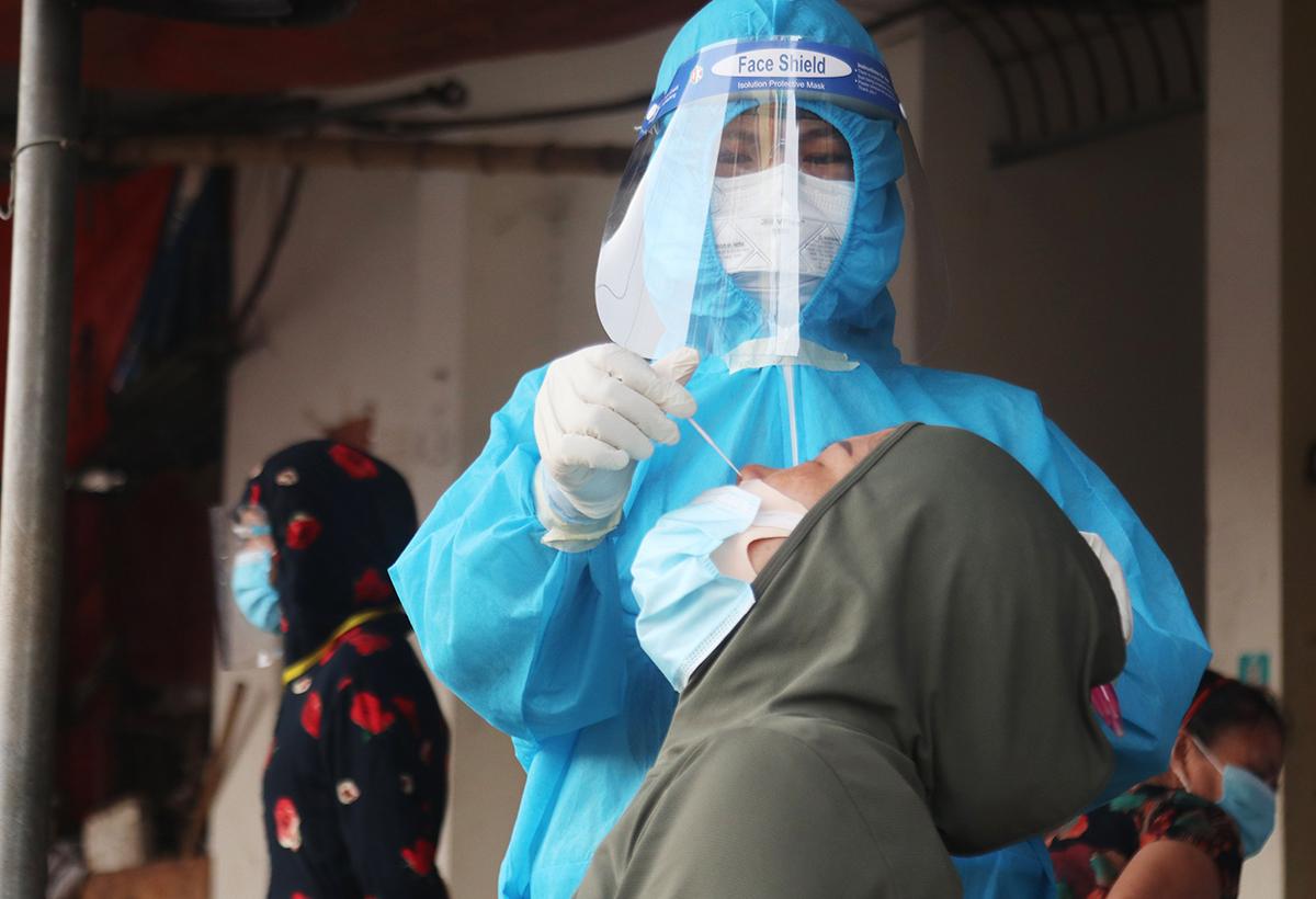 Nhân viên y tế lấy mẫu cho tiểu thương, chiều 23/6. Ảnh: Phương Linh