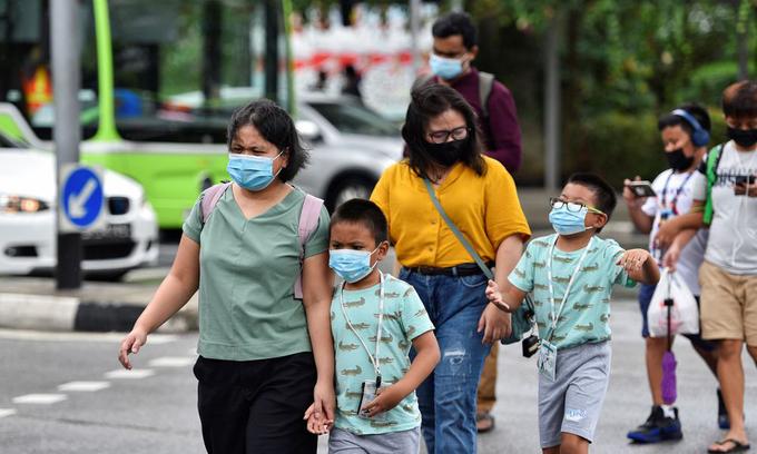 Người dân đeo khẩu trang trên đường phố Singapore hôm 14/5. Ảnh: Reuters.
