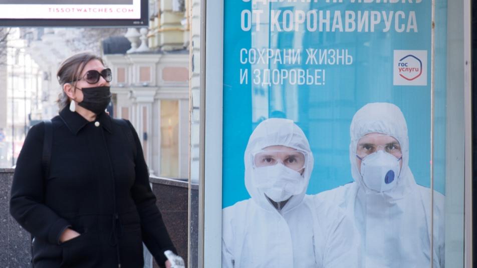 Một phụ nữ đi qua biển tuyên truyền người dân Nga đi tiêm chủng hồi đầu năm. Ảnh: TASS.