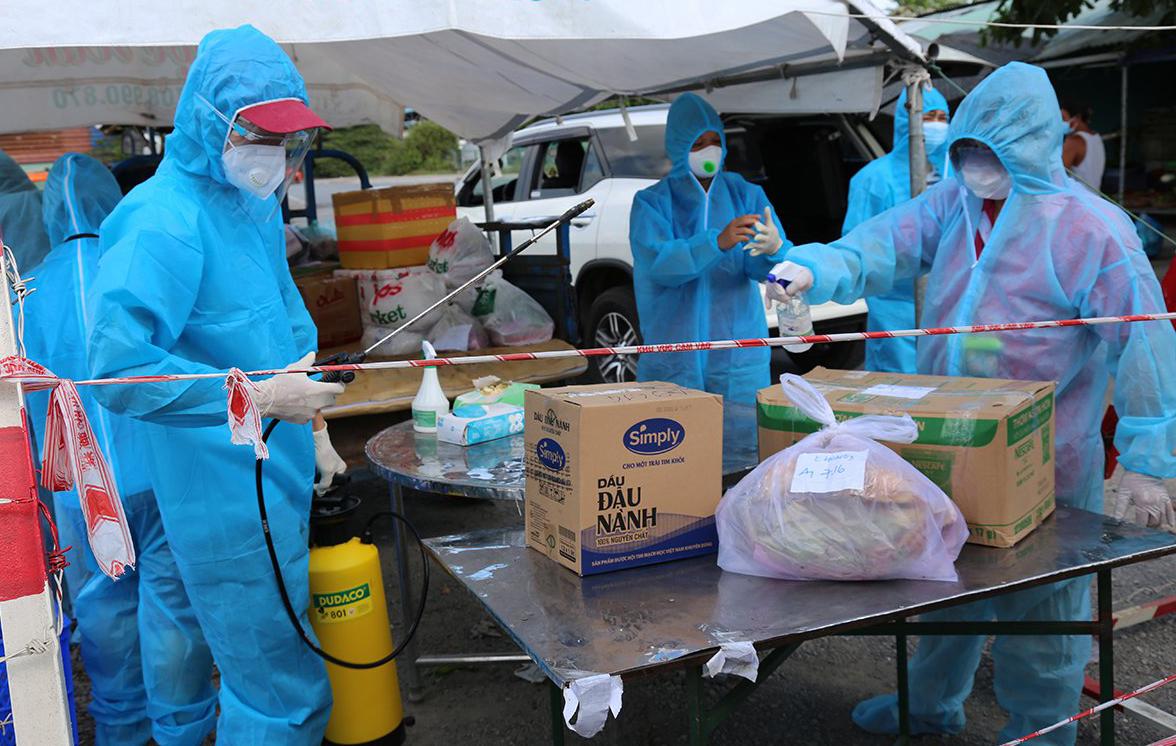 Đội chuyển hàng nhận thực phẩm, phun khử trùng trước khi chở vào cho người dân ở chung cư Ehome 3. Ảnh: Đình Văn