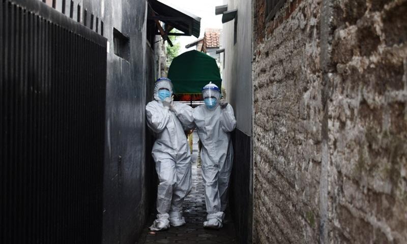 Nhân viên y tế di chuyển thi thể bệnh nhân Covid-19 chết tại nhà ở thành phố Bandung, tỉnh Tây Java, Indonesia hôm 23/6. Ảnh: AFP.