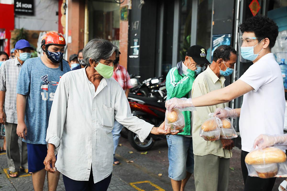 Người dân nhận đồ ăn miễn phí tại một điểm phát ở quận 1, ngày 18/6. Ảnh: Quỳnh Trần.