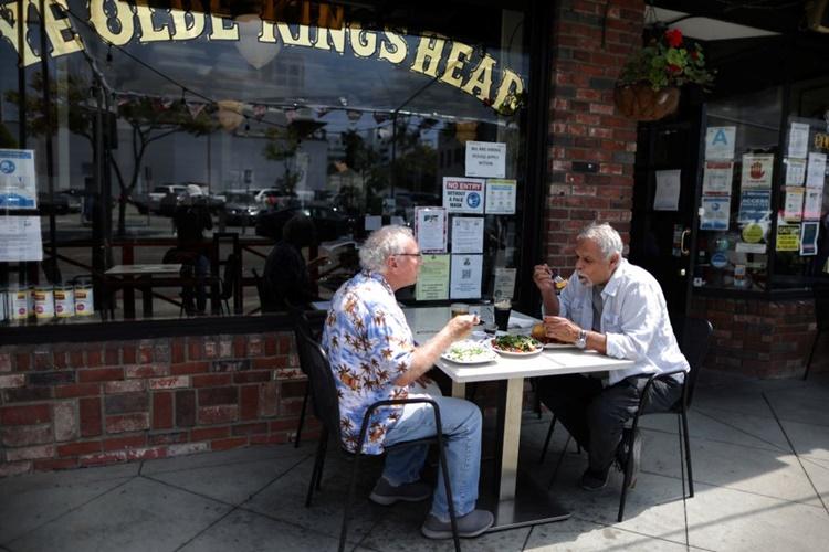 Khách ngồi dùng bữa bên ngoài một nhà hàng ở Santa Monica, Florida, ngày 6/5. Ảnh: Reuters.