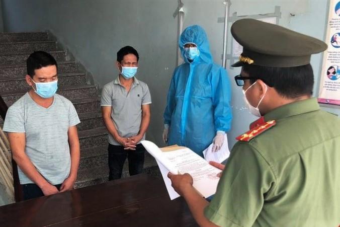 Hai tài xế Thủy (trái) và Nguyên nghe đọc lệnh bắt giam, ngày 26/6. Ảnh: Công an cung cấp.