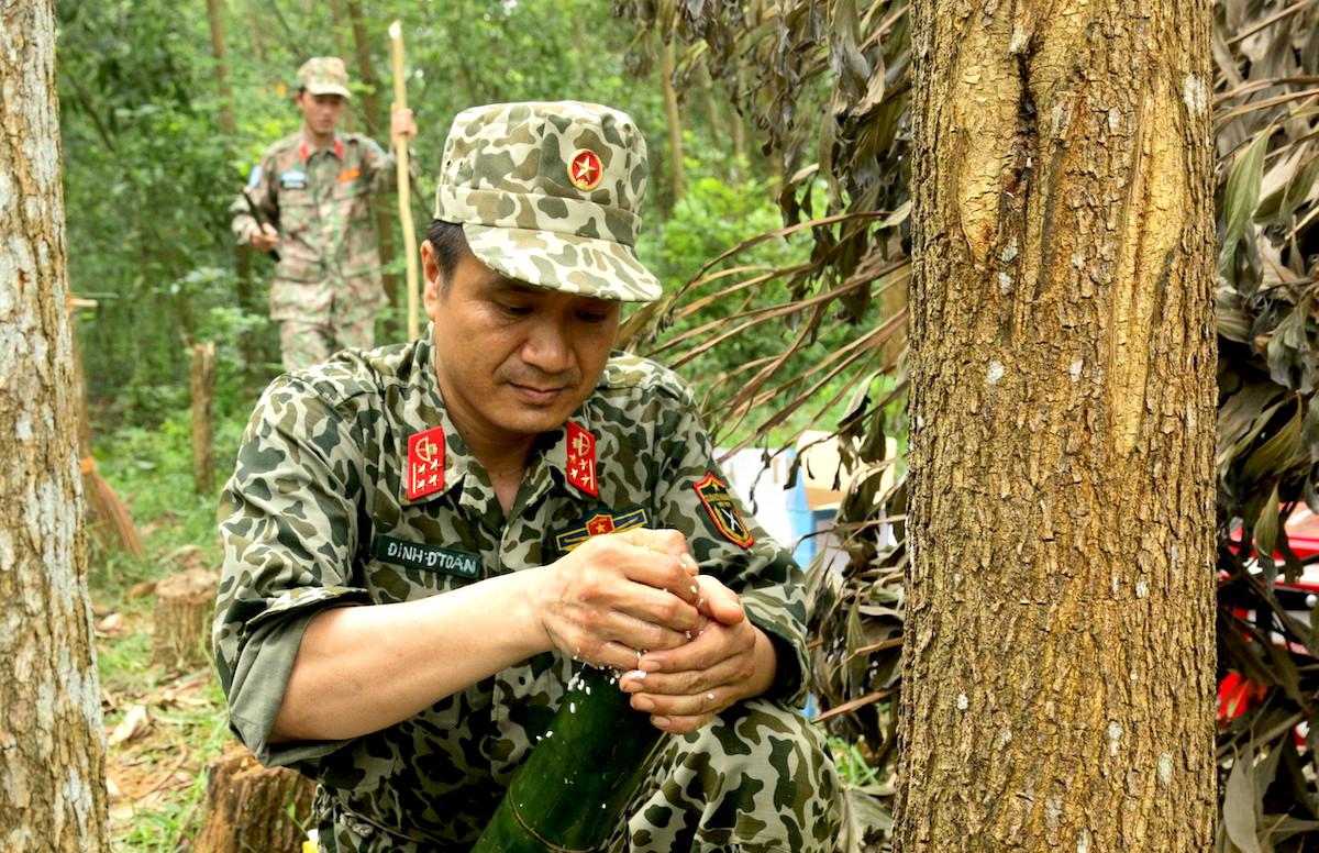 Đại úy Quân nhân chuyên nghiệp Đinh Đức Toán cho gạo vào thân tre để nấu cơm. Ảnh: Hoàng Thùy