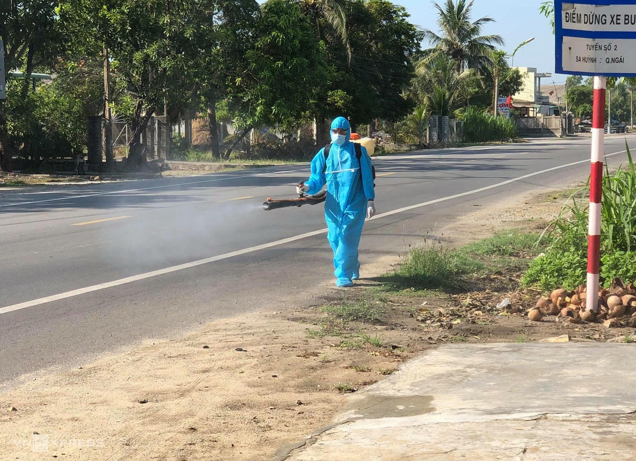 Nhân viên y tế phun thuốc khử quẩn ở trước nhà một bệnh nhân bên quốc lộ 1. Ảnh: Phương Trần.