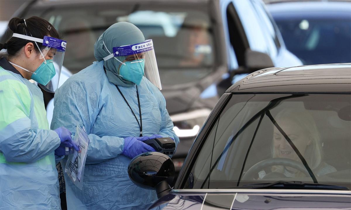 Nhân viên y tế Australia lấy mẫu xét nghiệm nCoV tại một trạm lưu động ở Sydney ngày 17/6. Ảnh: Reuters.
