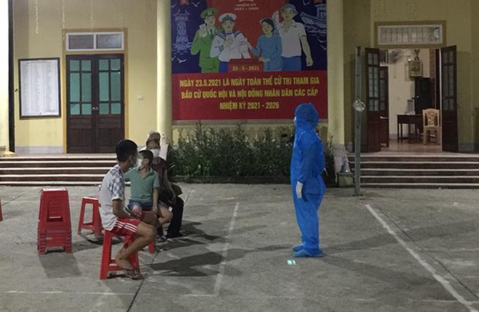 Chị Vân Anh trong trang phục bảo hộ lúc gặp lại hai con và bố mẹ chồng tại sân nhà văn hóa khối Tân Phượng, đêm 24/6. Ảnh: Hải Dương