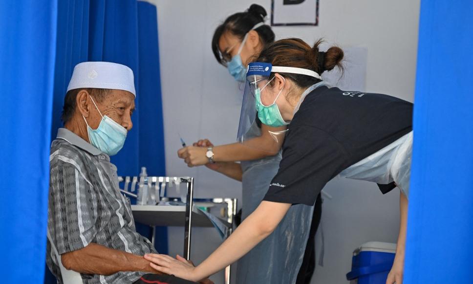 Nhân viên y tế trấn an một người đàn ông trước khi tiêm vaccine Covid-19 tại một điểm tiêm chủng ở Kuala Lumpur, Malaysia, hôm 21/6. Ảnh: AFP.