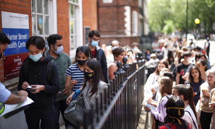 Người Anh xếp hàng chờ tiêm vaccine ở London, Anh tháng trước. Ảnh: Reuters.