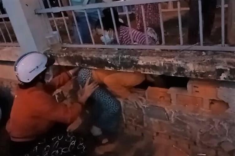 Các phụ nữ đang chui lỗ tường rào thoát ra bệnh viện, đêm 1/7. Ảnh: Cắt từ video người dân cung cấp