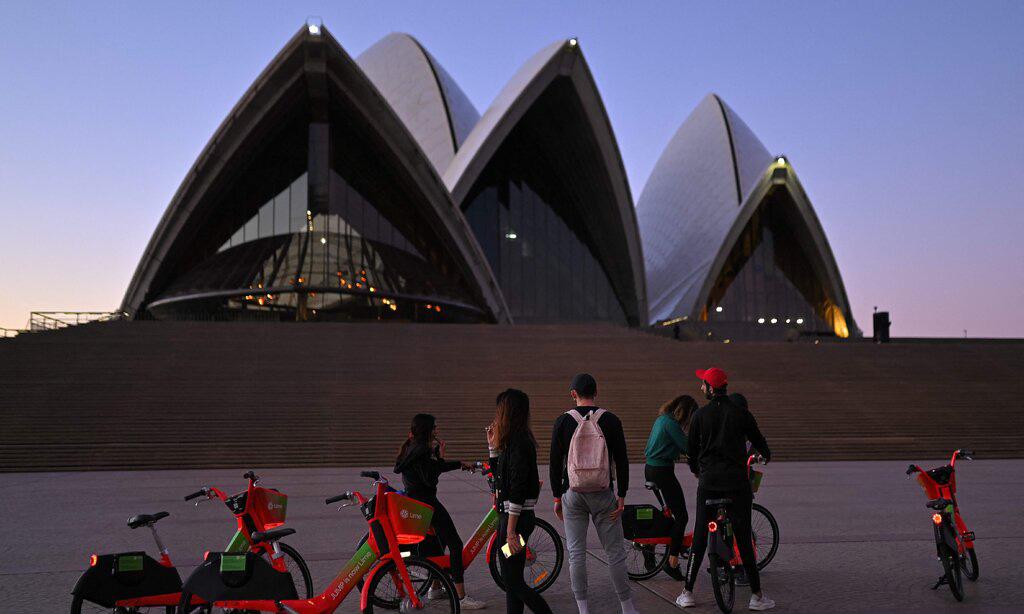Người dân đứng trước Nhà hát Opera Sydney, Australia, hôm 27/6. Ảnh: AFP.