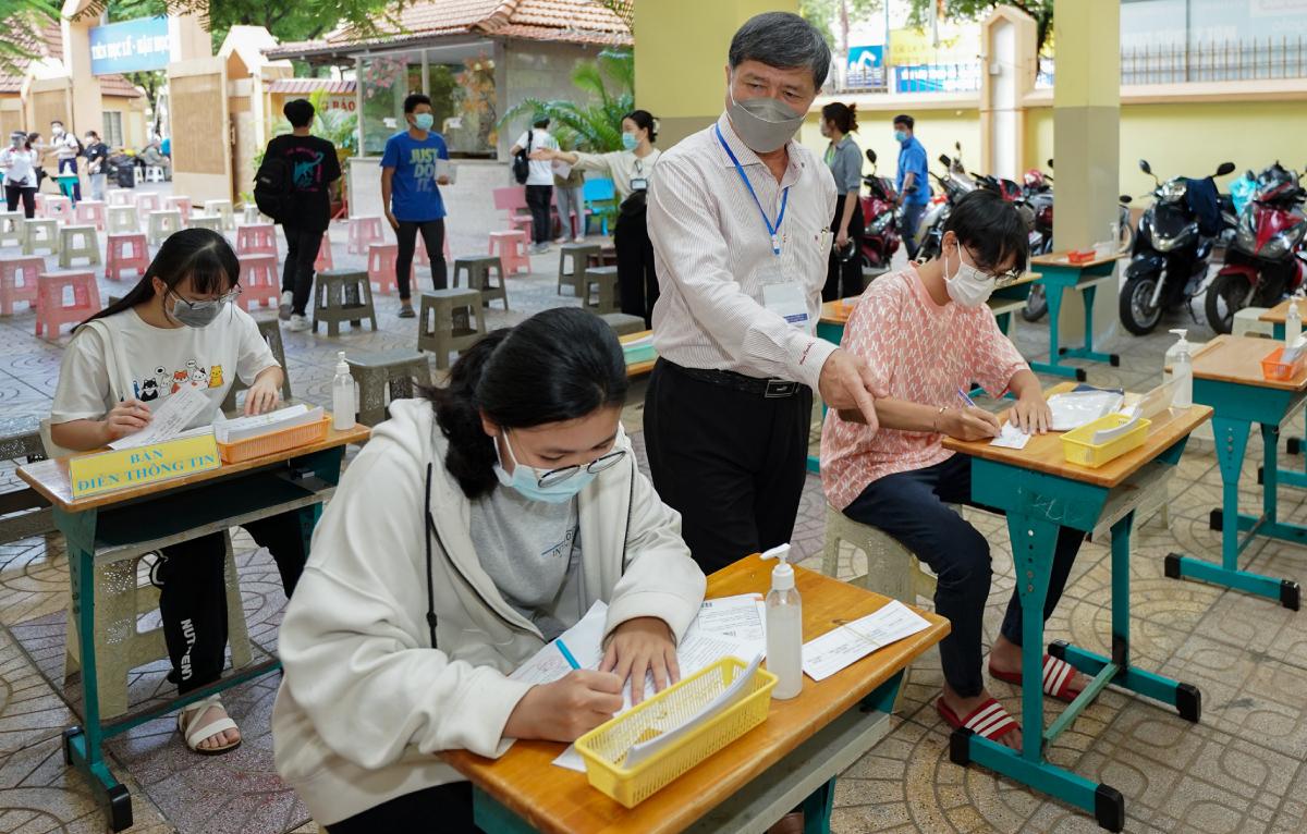 Phó giám đốc Sở Giáo dục và Đào tạo Nguyễn Văn Hiếu kiểm tra việc chuẩn bị lấy mẫu xét nghiệm tại điểm trường Tiểu học Nguyễn Bỉnh Khiêm. Ảnh: Mạnh Tùng.