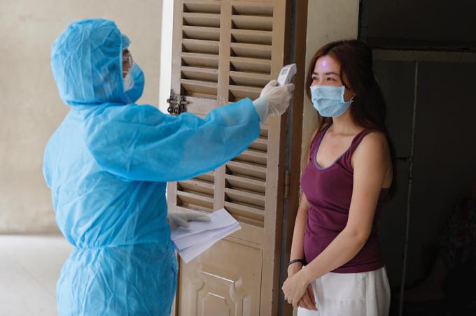 Nhân viên y tế kiểm tra sức khoẻ người cách ly tại ký túc xá Đại học Quốc gia TP HCM. Ảnh: Hữu Khoa.