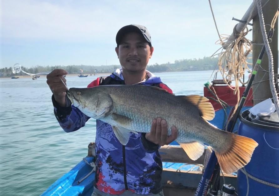 Anh Ánh cùng con cá chẽm 14kg câu được ở cảng Sa Kỳ. Ảnh: Như Đồng.