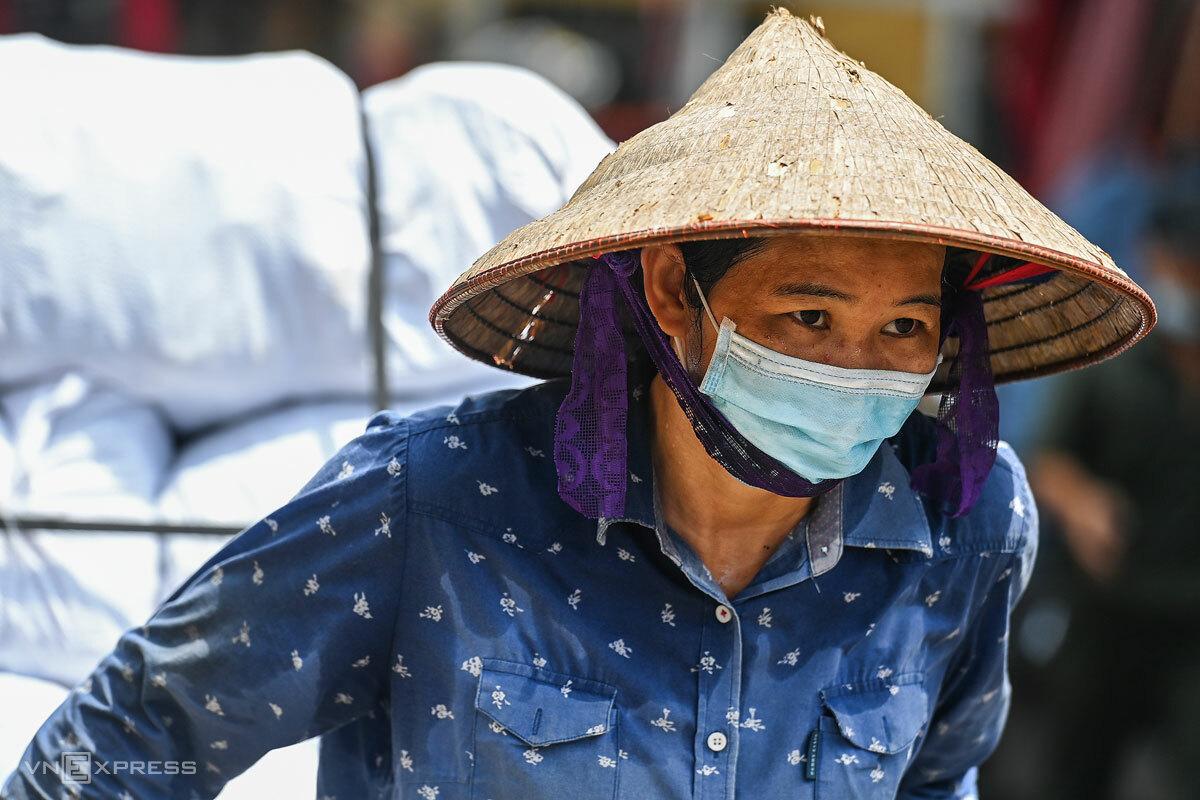 Nữ lao động kéo hàng thuê trong nắng nóng hơn 40 độ C ở Hà Nội, tháng 6/2021. Ảnh: Giang Huy