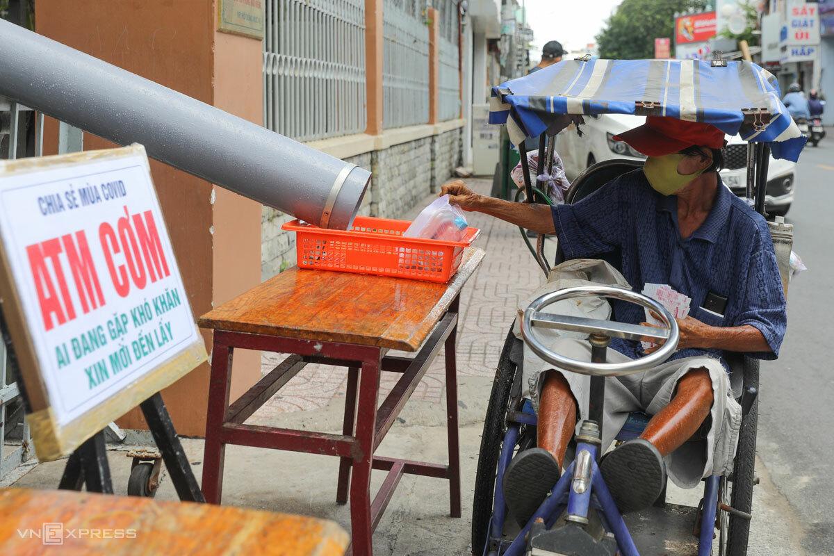 Người đàn ông bán vé số nhận cơm trưa 0 đồng tại ATM lướt ống đặt tại nhà thờ Tân Sa Châu, TP HCM. Ảnh: Quỳnh Trần