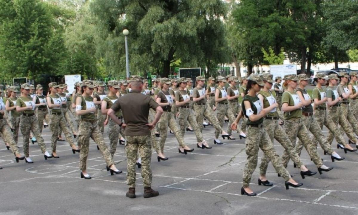 Một nam binh sĩ Ukraine đi giày cao cổ đế bằng giám sát các nữ học viên quân sự tập duyệt binh với giày cao gót. Ảnh: BQP Ukraine.