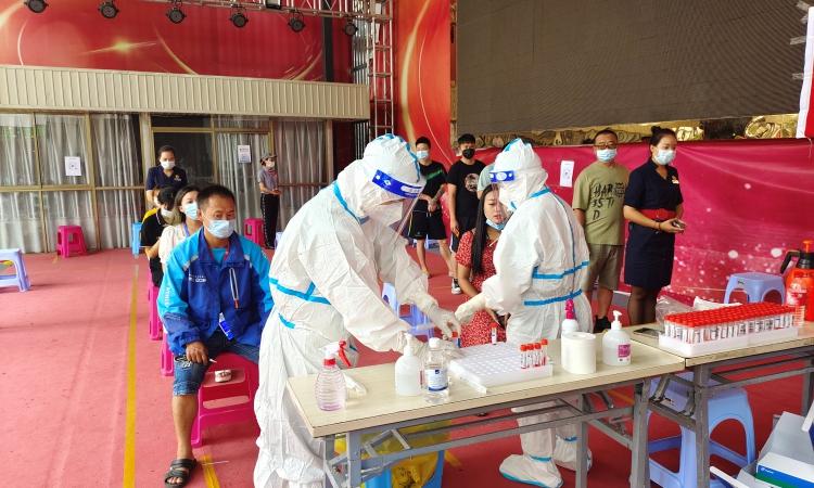 Người dân xếp hàng chờ xét nghiệm Covid-19 tại một khu dân cư ở thành phố Thụy Lệ, tỉnh Vân Nam, Trung Quốc, hôm 5/7. Ảnh: Reuters.
