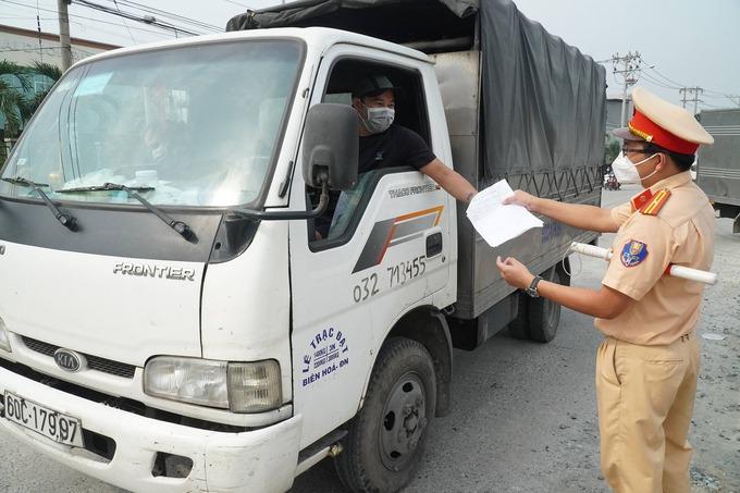 Cảnh sát giao thông kiểm tra giấy xác nhận xét nghiệm âm tính nCoV của tài xế tại chốt kiểm dịch trên quốc lộ 1K, TP Biên Hòa, sáng 5/7. Ảnh:Phước Tuấn
