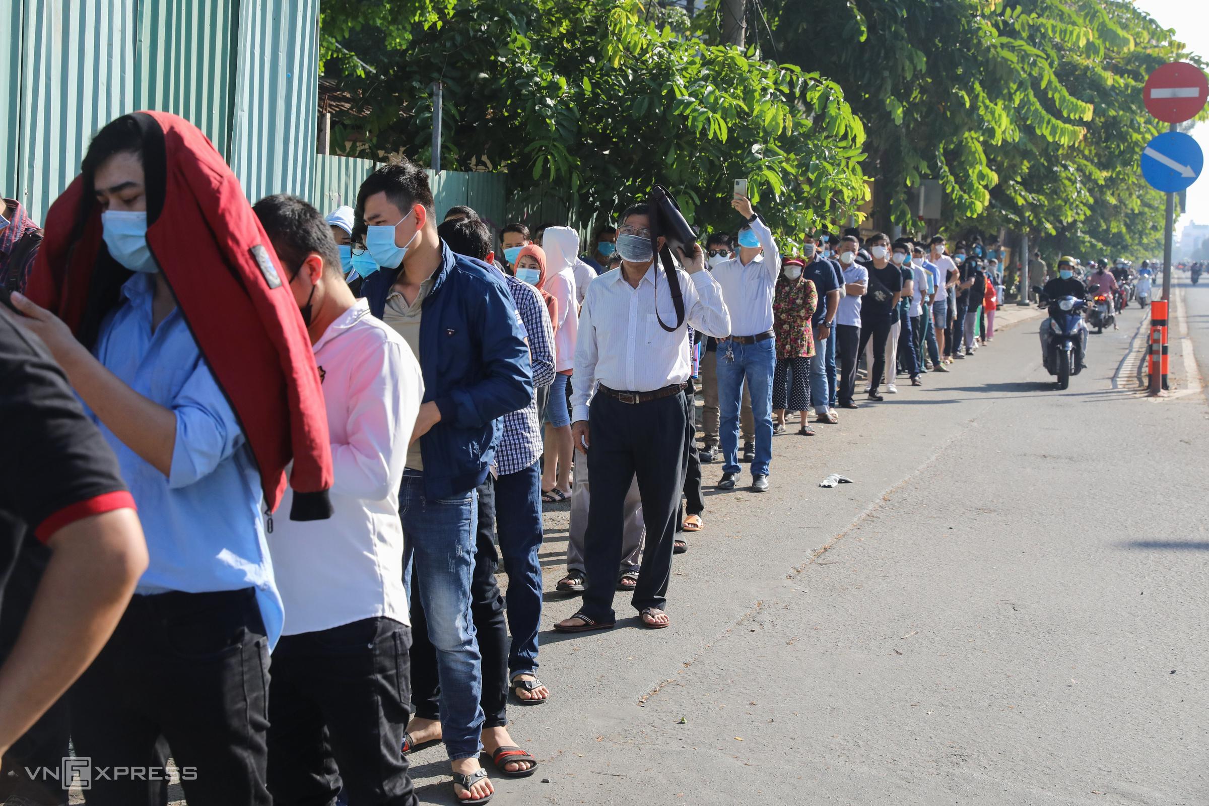 Dòng người xếp thành hàng dài trên vỉa hè và tràn ra cả lòng đường Nguyễn Thái Sơn, kéo dài khoảng 200 m tính từ cổng bệnh viện chờ xét nghiệm Ảnh: Quỳnh Trần.