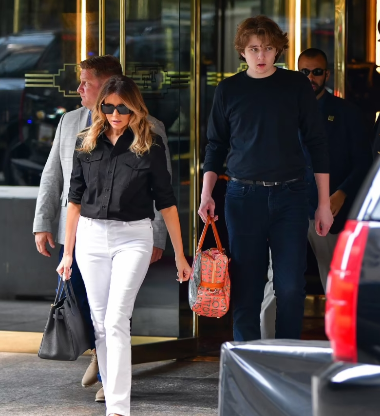 Barron Trump xách chiếc túi màu cam của mẹ khi cùng Melania rời khỏi Tháp Trump hôm 7/7. Ảnh: GQ