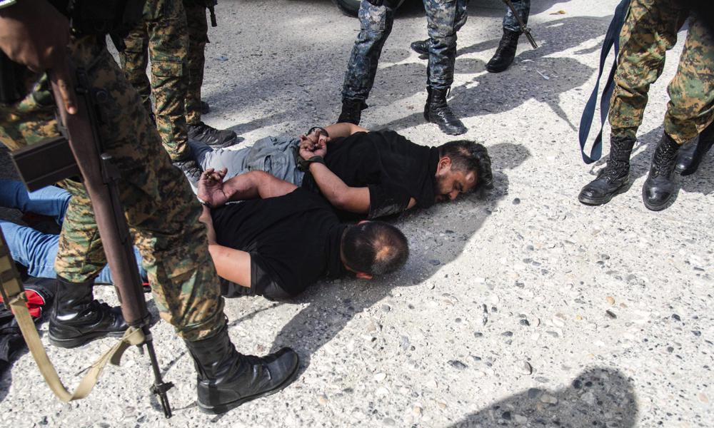 Các nghi phạm trong vụ ám sát Tổng thống Haiti Jovenel Moise nằm trên đất sau khi bị bắt tại thủ đô Port-au-Prince hôm 8/7. Ảnh: AP.