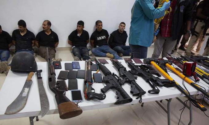 Vũ khí thu giữ từ nhóm nghi phạm vụ ám sát Tổng thống Haiti Jovenel Moise xếp trên bàn tại buổi họp báo ở Port-au-Prince hôm 8/7. Ảnh:AP.