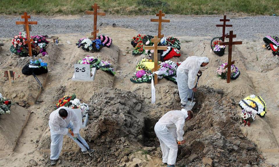 Các phu đào mộ mặc đồ bảo hộ nhằm phòng chống Covid-19 tại một nghĩa trang ở ngoại ô St. Petersburg, Nga, hôm 25/6. Ảnh: Reuters.