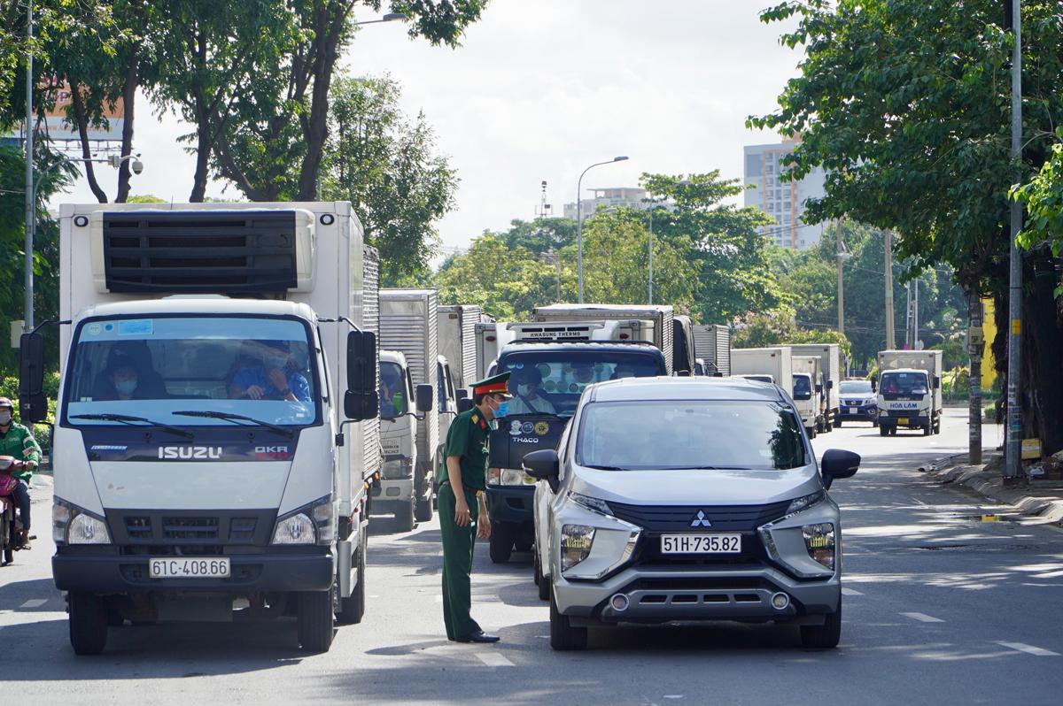 Lực lượng chức năng kiểm tra giấy tờ tài xế tại chốt kiểm soát trước Bến xe Miền Đông trên đường Đinh Bộ Lĩnh, quận Bình Thạnh, sáng 10/7. Ảnh: Gia Minh.