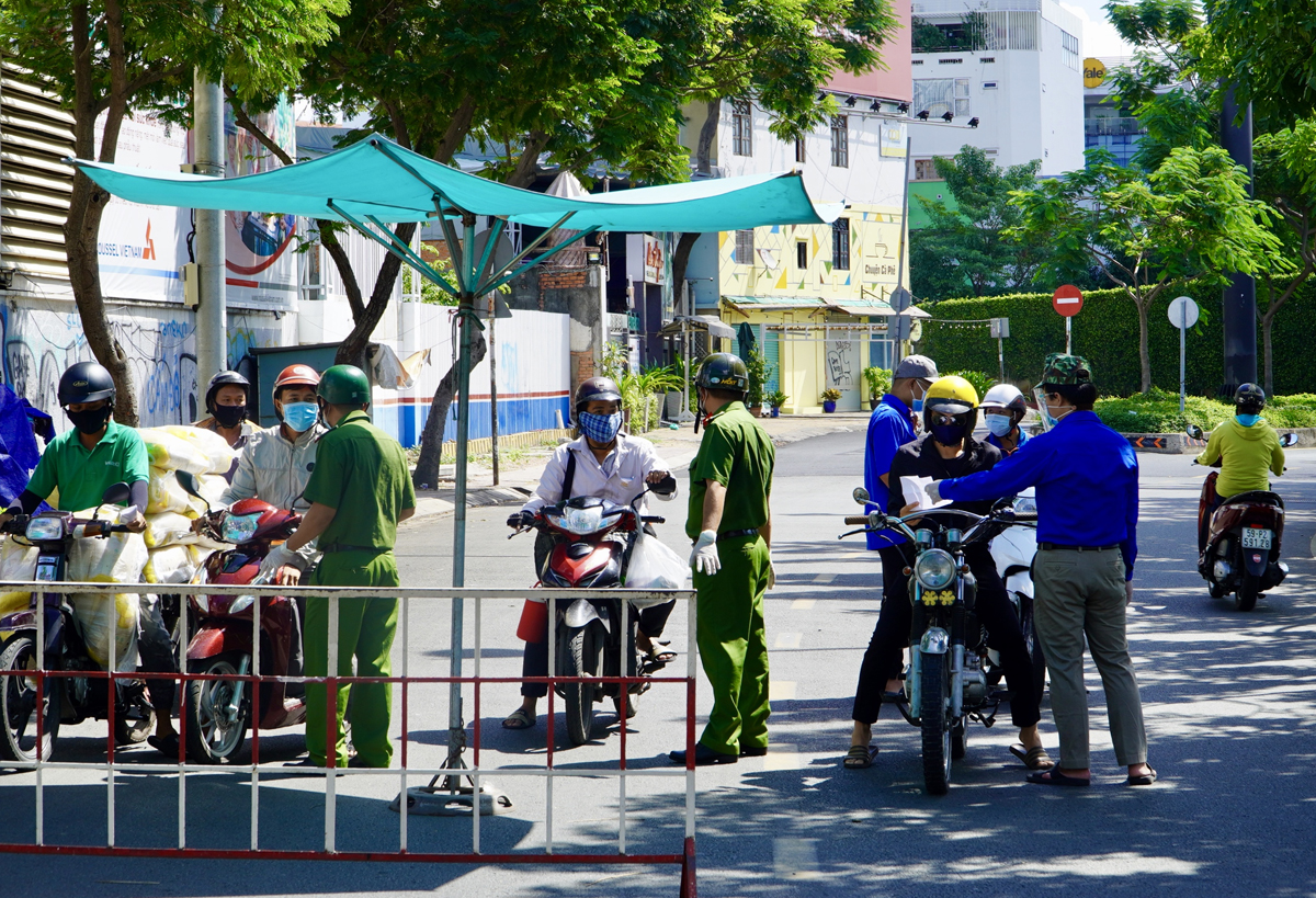 Cảnh sát kiểm soát người qua lại tại chốt trên đường Trường Sa, quận Phú Nhuận, sáng 10/7. Ảnh: Gia Minh.