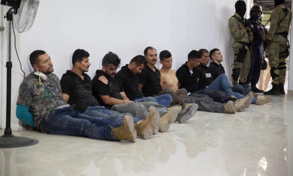 Nhóm nghi phạm trong vụ ám sát Tổng thống Haiti Jovenel Moise bị còng tay và ngồi dựa vào tường tại buổi họp báo ở thủ đô Port-au-Prince hôm 8/7. Ảnh: AP.