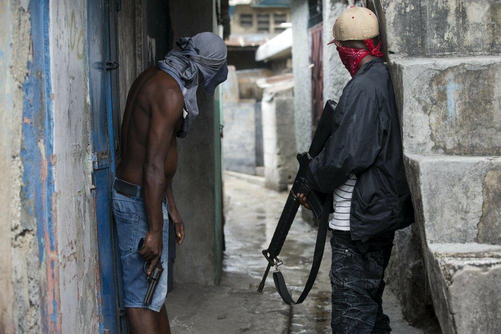 Hai tay thành viên một băng đảng ở Haiti cầm súng cảnh giới địa bàn hoạt động ở khu ổ chuột La Saline, thủ đô Port-au-Prince của Haiti vào tháng 5/2019. Ảnh: AP.